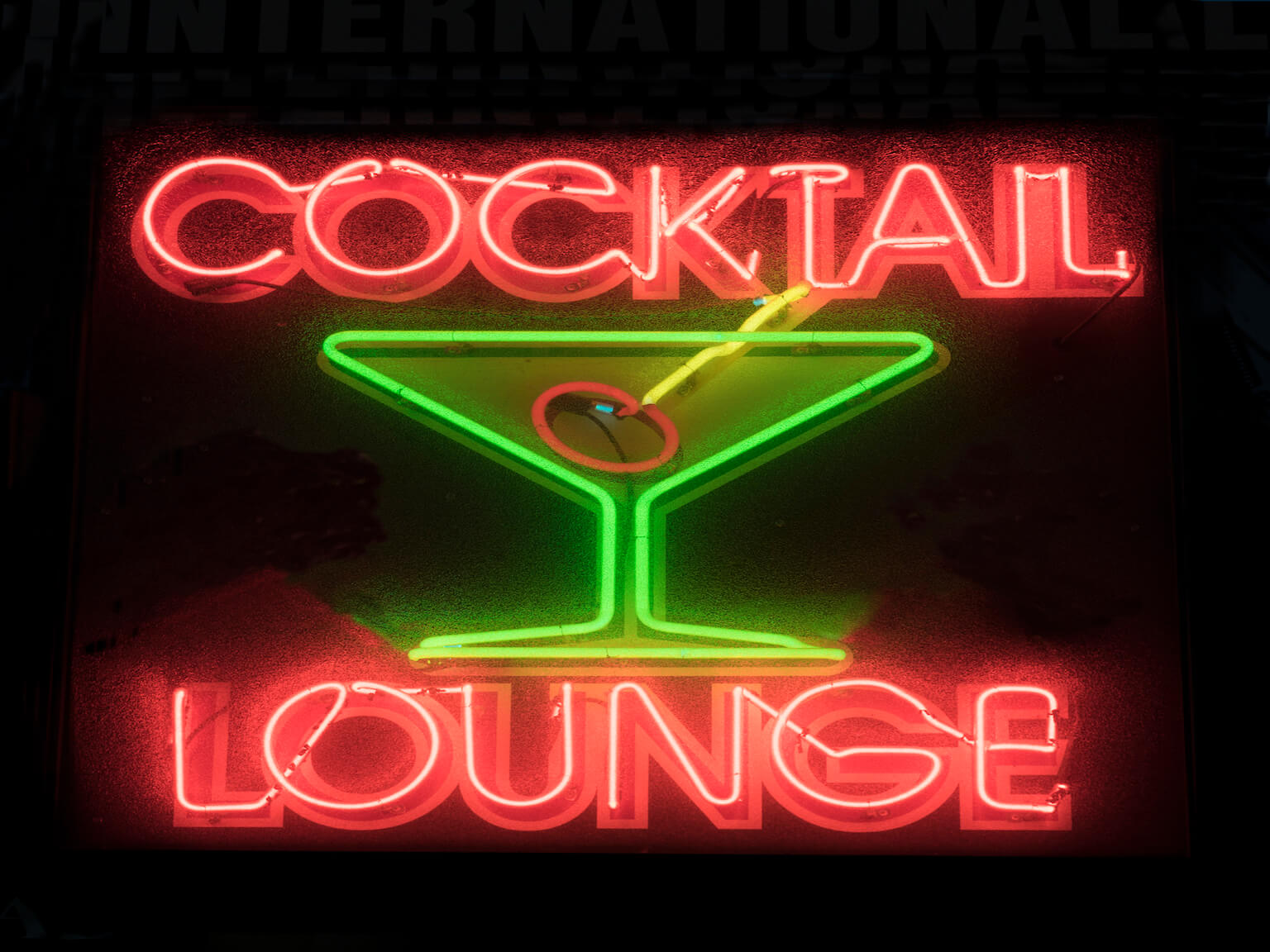 A red and green neon sign for a bar.